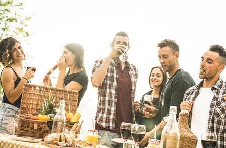 Young friends having fun outdoors drinking red wine and talking at barbecue party - Happy people eating local food at country side restaurant - Youth friendship concept on bright backlight filter Stock Photo
