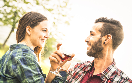 Happy young couple drinking red wine at vineyard farmhouse - Young man looking at beautiful woman eyes - People relationship concept with boyfriend and girlfriend having fun together - Bright filter Stock Photo