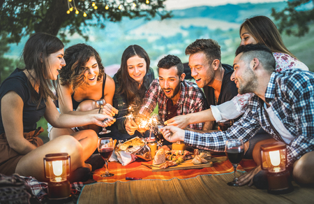 Happy friends having fun with fire sparkles - Young people millennials camping at picnic after sunset - Young people enjoying wine at summer barbecue party - Youth friendship concept on night mood Stock Photo