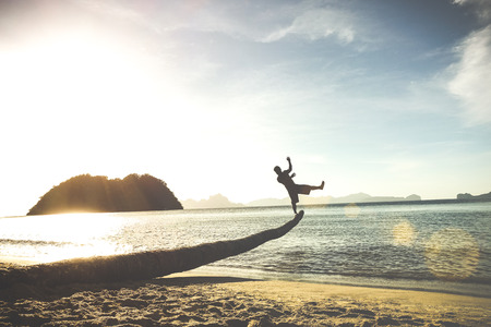 Silhouette of traveler guy on funny jump from palm - Travel wanderlust concept with man having fun at Las Cabanas beach in El Nido Palawan - Soft tilted horizon and vintage turquoise pastel filter Stock Photo