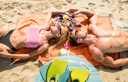 Top view of young couple vacationer having fun and relaxing on tropical Phuket beach in Thailand with coconut drink - Active youth love and travel concept around world - Bright warm color filter tones Stock Photo