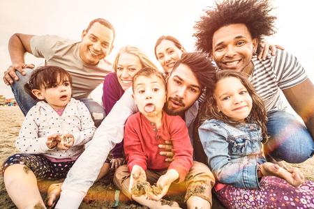 Szczęśliwe rodziny wielorasowe robiące selfie na plaży, robiące śmieszne miny - Wielokulturowa koncepcja radości i miłości z mieszanymi rasami, które bawią się na świeżym powietrzu o zachodzie słońca - Jasny pastelowy filtr podświetlenia