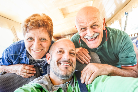 Senior happy couple with son taking selfie at boat trip in Laos - Adventure travel in south east asia - Elderly and family concept of love sharing moments with parents - Warm vintage filtered look Stock Photo