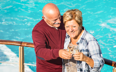 Happy senior retired couple having fun outdoors at travel vacation - Love concept of joyful elderly and retirement lifestyle with man drinking white wine with wife at pool - Warm bright filter