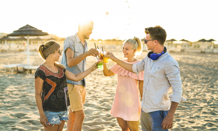 Group of happy friends millennial  having fun at beach party drinking fancy cocktails at sunset - Summer joy and friendship concept with young people on vacation - Warm sunshine filtered color tones
