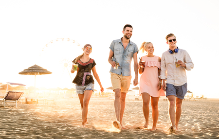 Group of happy friends having fun at seaside sunset - Summer vacations and friendship concept with young people millennials walking at beach - Warm sunshine filtered color tone with focus on left girl Stock Photo