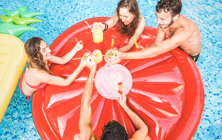 Top view of happy friends drinking cocktails at swimming pool party - Vacation concept with happy guys and girls having fun in summer day at luxury resort - Young people cheering at tropical beach Stock Photo