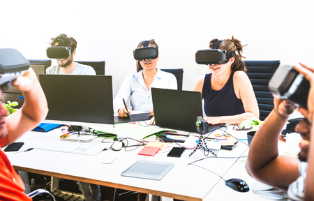 Group of young people employee workers having fun with vr virtual reality goggles in startup studio - Human resource business concept on millennials working time - Start up entrepreneurs at office Stock Photo