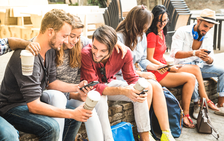 Multiracial millennials group using smart phone at city college backyard - Young people addicted by mobile smartphone - Technology concept with connected trendy friends - Warm vibrance sunshine filter Stock Photo