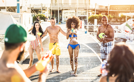 Multiracial happy friends having crazy fun with waterfight battle at summer location - Carefree vacation concept with young people millennials using water gun at beach docks - Warm backlight filter Stock Photo