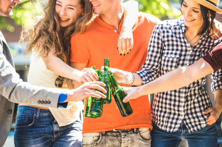 Happy friends group drinking and toasting bottled beer on sunny day outdoors - Friendship concept with young people millennials enjoying summer time together and having fun at park - Focus on bottles