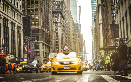 NEW YORK - MARCH 27, 2015: rush hour with yellow cab on 7th Av crossroad with West 35th in Manhattan at sunset - Seventh Avenue is southbound below Central Park and a two way street north of the park