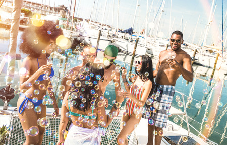 Multiracial friends group having fun drinking wine at sail boat party - Friendship concept with young multi racial people on sailboat - Happy travel lifestyle on luxury location - Warm bright filter Stock Photo