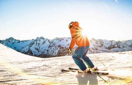 Professional skier athlete skiing at sunset on top of french alps ski resort - Winter vacation and sport concept with adventure guy on mountain top riding down the slope - Warm bright sunshine filter Stock Photo