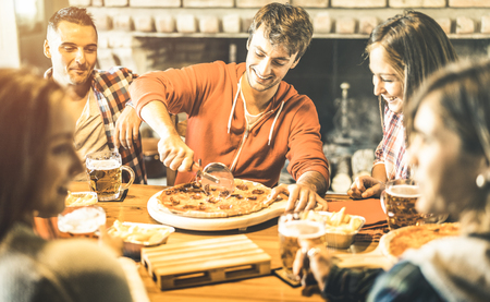 Happy friends group eating pizza at chalet bar restaurant - Friendship concept with young people enjoying time together and having genuine fun at rustic pizzeria  - Focus on guy cutting slices Stock Photo