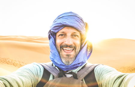 Young man solo traveler taking selfie at Erg Chebbi desert dune near Merzouga in Morocco - Adventure wanderlust concept on world famous nature wonder in Maroc - Warm bright sunset color filtered tones Фото со стока - 111828642