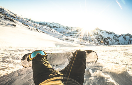 Snowboarder sitting at sunset on relax moment in european alps ski resort - Winter sport concept with guy and snowboard on mountain top ready to ride - Legs point of view on vintage contrast filter Stock Photo