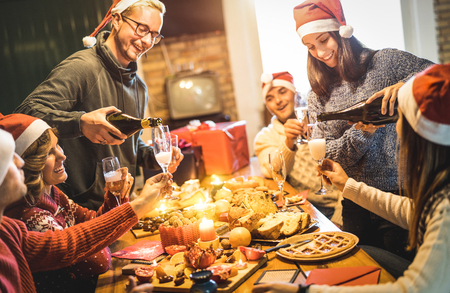 Friends group with santa hats celebrating Christmas with champagne and sweets food at home dinner - Winter holidays concept with people enjoying time and having fun eating together - Warm filter