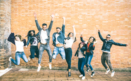 Happy friends millennials jumping and cheering against brick wall in the city - Friendship lifestyle and team concept with young people millenial having fun together - Teal and orange vintage filter Фото со стока