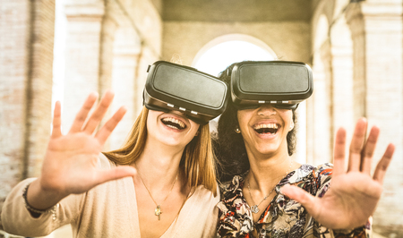 Girlfriends playing on vr glasses outdoors - Virtual reality and wearable tech concept with young people having fun together with headset goggles - Generation z digital trends - Retro contrast filter