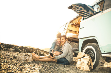 Hipster couple traveling together on oldtimer mini van transport - Travel lifestyle concept with indie people on minivan adventure trip having fun with mobile smart phone - Warm desaturated filter Stockfoto