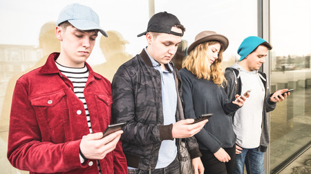 Group of multicultural friends using smartphone at university college break - Fashion millennials people addicted by mobile smart phones - Technology concept on always connected time - Filter image