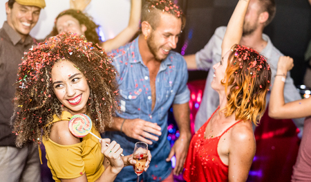 Multiracial happy friends having fun drinking wine at eve celebration - Young people dancing at after party in night club - Friendship concept on cool entertainment mood - Focus on left latin girl
