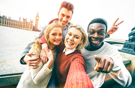 Happy multiracial friends group taking selfie in London at european trip - Young people addicted by sharing stories on social network community - Millennials lifestyle concept on vivid contrast filter Stock Photo
