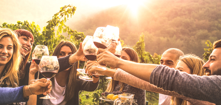Young friends having fun outdoors - Happy people enjoying harvest time together at farmhouse winery countryside - Youth and friendship concept - Hands toasting red wine glass at vineyard before sunset