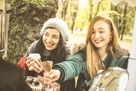 Happy girlfriends best friends sharing time together outdoors at coffee takeaway vendor in winter season - Female friendship concept with joyful women having fun on warm clothes - Focus on right girl