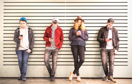 Friends group using smartphone against wall at university college backyard break - Young people addicted by mobile smart phone - Technology concept with always connected millennials - Bright filter Stock Photo