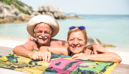 Senior couple vacationer having genuine fun on Koh Samui tropical beach in Thailand - Excursion tour in exotic scenario - Active elderly and travel concept around the world on warm bright sunny filter