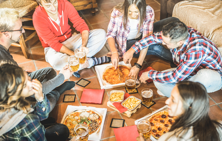 Happy friends eating take away pizza at home after work - Friendship concept with young people enjoying time together and having genuine fun in start up office - Focus on beers and french fries 스톡 콘텐츠