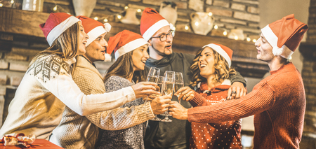 Friends group with santa hats celebrating Christmas with champagne wine toast at home dinner - Winter holidays concept with young people enjoying time and having fun together - Focus on glasses Stock Photo