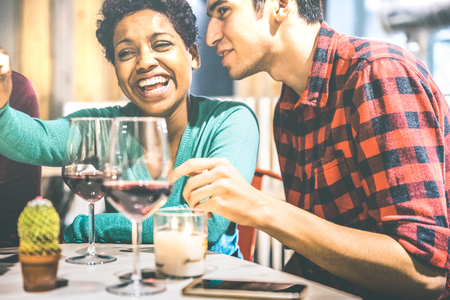 Happy multiracial couple of lovers drinking red wine at fashion restaurant - Handsome man talking funny with beautiful woman - Relationship concept with boyfriend and girlfriend on vintage filter