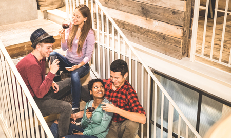 Top side view of multi racial happy friends tasting red wine and having fun at fashion bar winery - Multicultural friendship concept with young people enjoying time on stairs at home drinking together Stock Photo