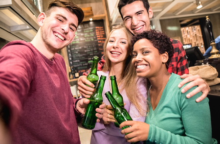 Multiracial friends taking selfie and drinking beer at fancy brewery restaurant - Friendship concept with young people enjoying time together having drunk fun at fashion bar - Focus on middle girl Stock Photo