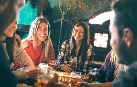 Group of happy friends drinking beer at brewery bar restaurant - Friendship concept with young millenial people enjoying time together having fun vintage pub - Focus right woman - High iso image Stock Photo