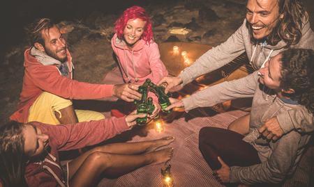 Young hipster friends having fun together at night beach party with campfire light - Friendship travel concept with young people traveler drinking beer at summer surf camping - High iso image Stock Photo