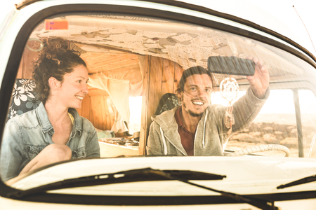 Indie couple ready for roadtrip on oldtimer mini van transport - Travel lifestyle concept with young hippie people having fun traveling on minivan adventure trip - Warm bright filter Stockfoto - 113628222