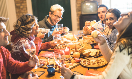 Front view of friends group tasting christmas sweets food and having fun at home drinking champagne sparkling wine - Winter holidays concept with people enjoying time eating together - Warm filter Stock Photo