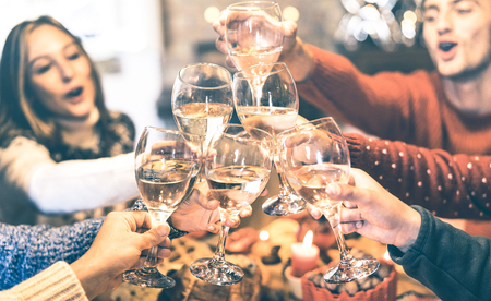 Friends group celebrating Christmas toasting champagne wine at home dinner - Winter holiday concept with young people enjoying time and having fun together - Azure vintage filter with focus on glasses Banque d'images