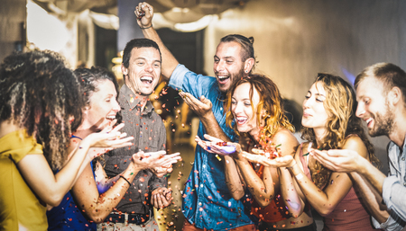Multiracial happy friend having fun at new years eve celebration - Young people blowing confetti at after party in night club - Friendship concept on cool entertainment mood - Focus on blue shirt guy