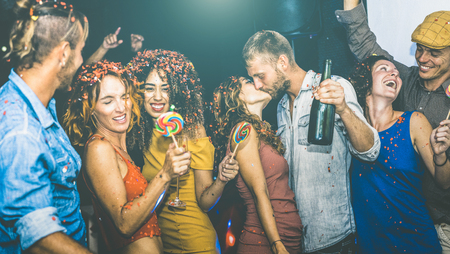 Happy friends having multiracial fun at new years eve celebration - Young people drinking and dancing at after party in night club - Friendship concept on drunk mood - Focus on yellow cloth woman