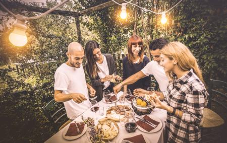 Amis heureux s'amusant à manger de la nourriture locale à la fête du jardin - Concept d'amitié et de vacances avec des gens ensemble à la cave viticole de la ferme - Filtre vintage chaud avec éclairage électrique artificiel