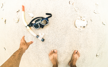 Point of view of hand picking up snorkeling mask at the beach - Adventure travel lifestyle enjoying fun activity at sea excursion adventure - Trip around world nature wonders Stock Photo