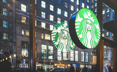 NEW YORK - MARCH 25, 2015: Starbucks sign at cafe shop by night with glass reflections on Nyc nightscape - The enterprise is an american coffee company and coffeehouse chain founded in 1971 Editorial
