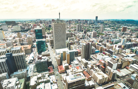 Aerial view of skyscrapers cityscape in business district of Johannesburg - Architecture concept with modern building skyline in South Africa big city - Landscape on desaturated dramatic filtered look Imagens