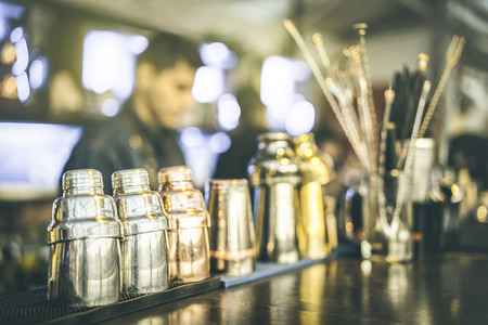 Blurred defocused view of barman preparing drinks at speakeasy cocktail bar on happy hour - Mixology concept with blurry bartender at work - Warm vintage retro filter with focus on second left shaker Foto de archivo - 115983841