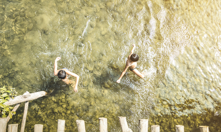 Unrecognizable children swimming in Nam Song river in Vang Vieng - Real everyday healthy life and fun of playful kids in Laos PDR countryside region - Bright vintage filter